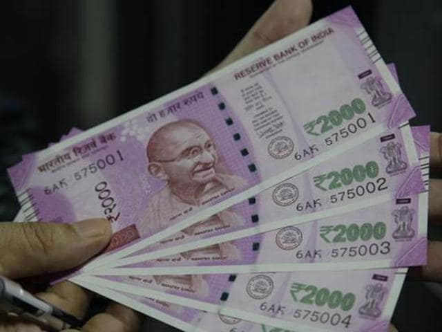 A man shows new Rs 2000 banknotes he received after exchanging demonetised notes in Jammu.