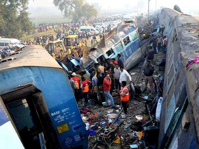 Rescue workers search for survivors at the site of a train derailment in Kanpur Dehat district.
