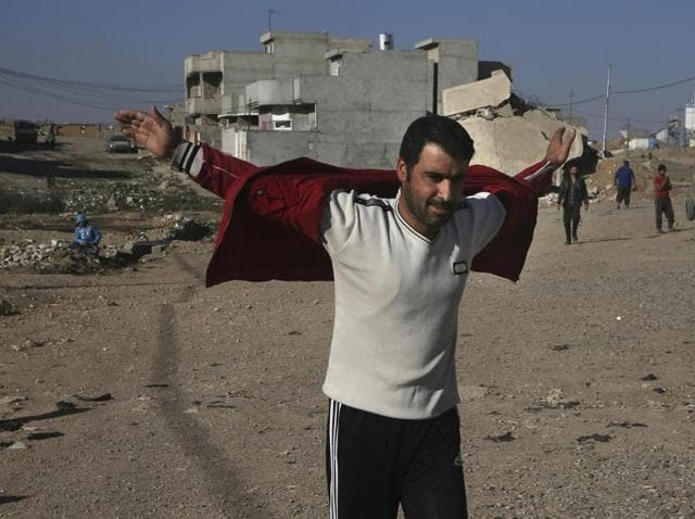 An Iraqi man opens his jacket and and raises his hands to show the army that he's not wearing an explosive belt, as he arrives to receive food supplies in Mosul on Saturday.