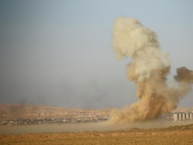 Smoke rises from clashes during a battle with Islamic State militants at the airport of Tal Afar west of Mosul, Iraq.