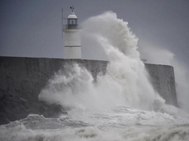 Waves crash against the harbour wall as Storm Angus passes western France  and southern England .