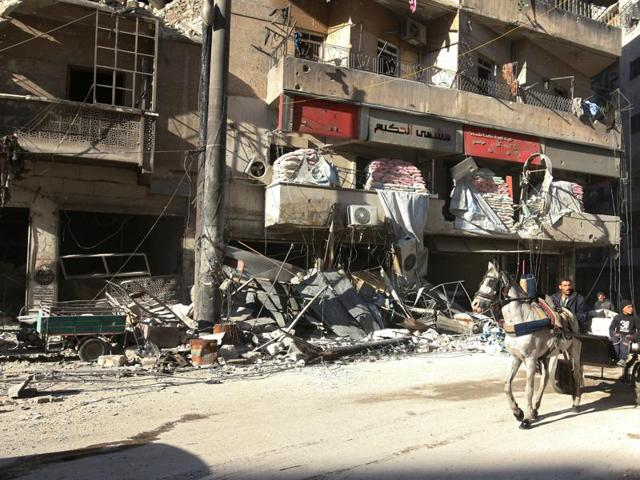 People ride a cart pulled by a horse near the damaged al-Hakeem hospital, in the rebel-held besieged area of Aleppo on Saturday.