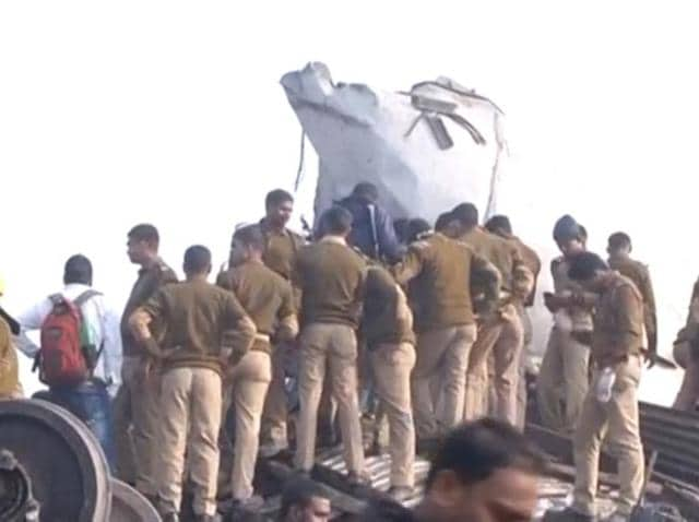 Police officers and people gather at the site where a train was derailed in Kanpur.