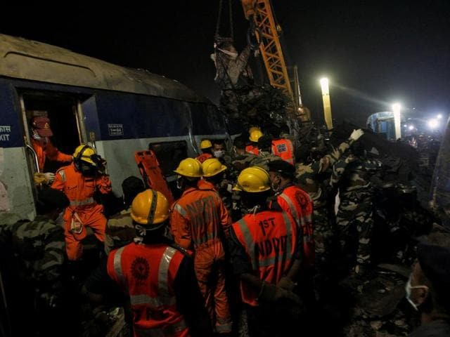 Rescue workers search for survivors at the site of a train derailment in Pukhrayan, south of Kanpur city, on November 20, 2016.