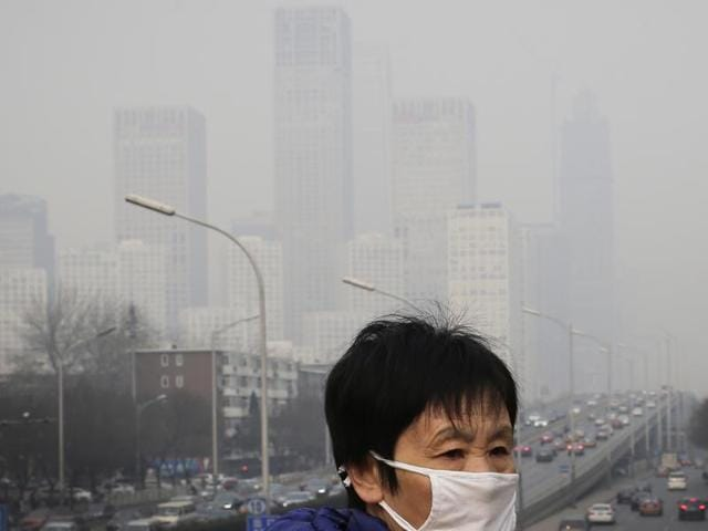 A woman wearing a mask for protection against pollution walks on a pedestrian overhead bridge as office buildings are shrouded with smog in Beijing.