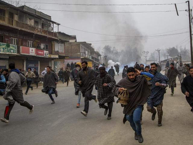 Kashmiri villagers run for cover from tear gas shells and pellets fired at them by Indian police during a protest near the funeral of Rayees Ahmad Dar, a suspected militant of Lashkar-e-Taiba (LeT) in Kakpora village south of Srinagar, Indian controlled Kashmir on Sunday.