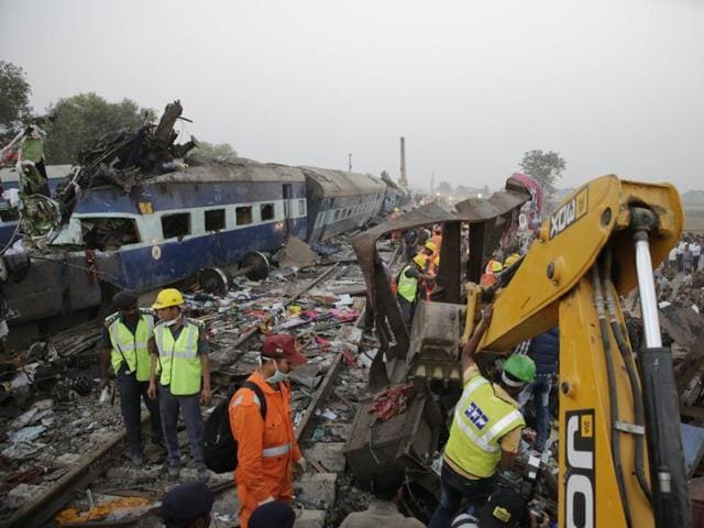 The body of a victim lies buried amid the mangled remains of crashed bogies after 14 coaches Indore-Patna  express near Pukhrayan village,Kanpur Dehat district. More than 120 passengers have been killed and above 100 injured.