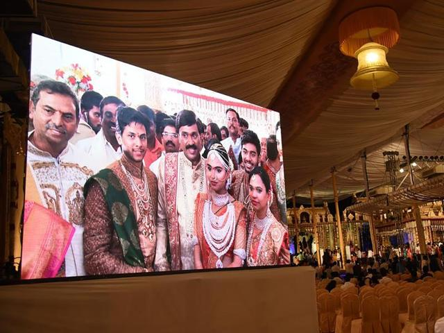 Gali Janardhan Reddy is seen on a big screen as he poses with his daughter Bramhani and son-in-law, Rajeev Reddy during their wedding at the Bangalore Palace Grounds in Bangalore.
