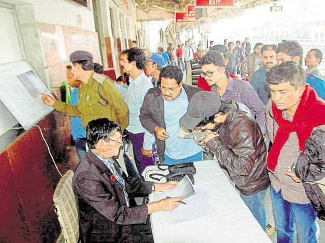 People at Bhopal Railway Station line up to seek information about trains after the accident.