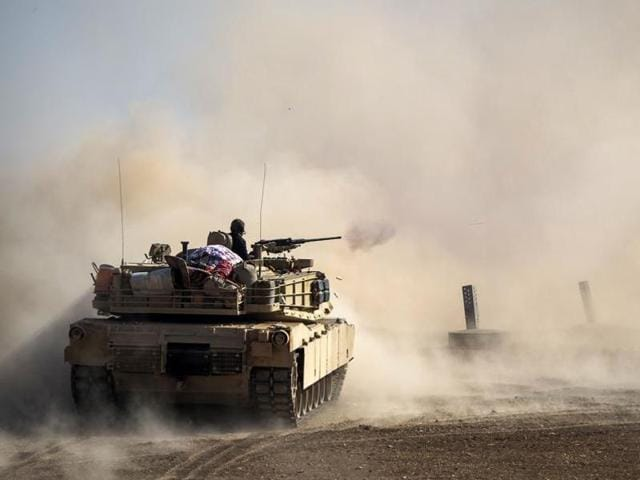 Shia fighters ride on a tank heading toward the airport of Tal Afar during a battle with Islamic State militants in Tal Afar west of Mosul, Iraq.