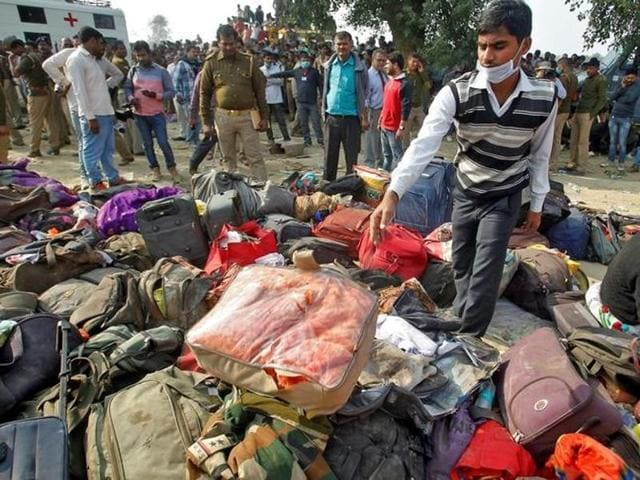 A man sorts through luggage at the site of the train accident in Pukhrayan, Kanpur.(Reuters Photo)