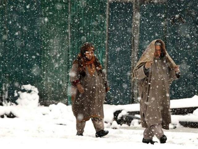Kashmiri people walking in the snow in Srinagar.
