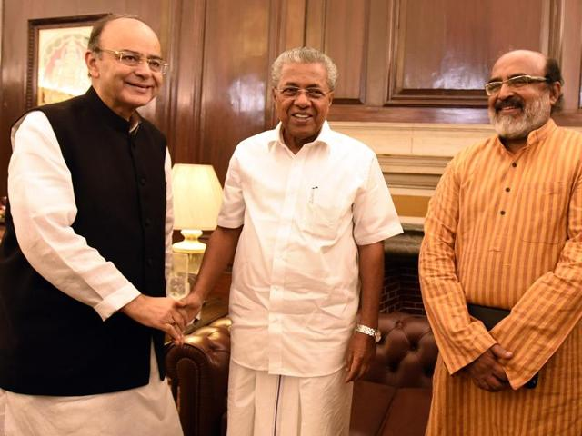 Union finance minister Arun Jaitley  shaking hands with Kerala finance minister Thomas Isaac in the presence of Kerala chief Minister Pinarayi Vijayan.