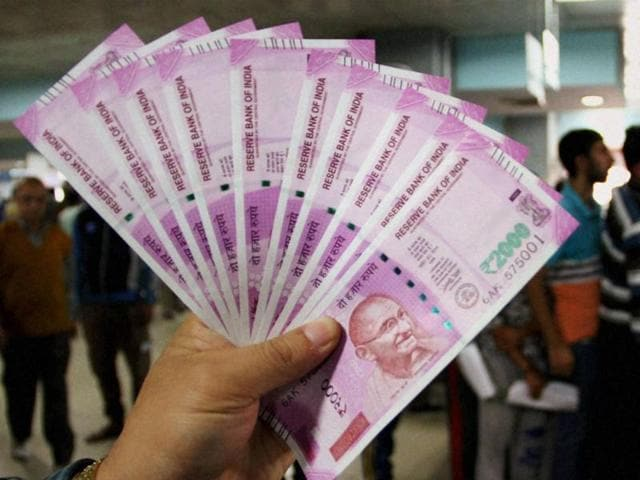 A bank officer shows new Rs 2000 notes in Jammu.
