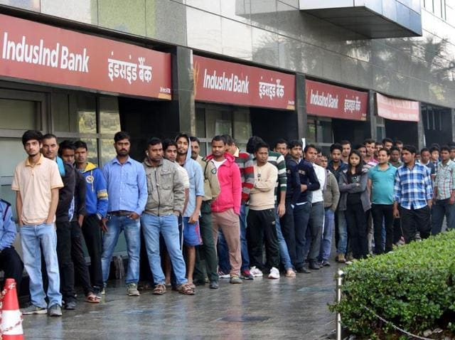 People stand in long queue to withdraw cash from an ATM at MG road in Gurgaon.