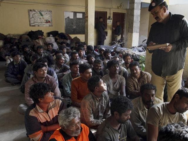 A Pakistani police officer collects information from arrested Indian fishermen at a police station in Karachi on Sunday.