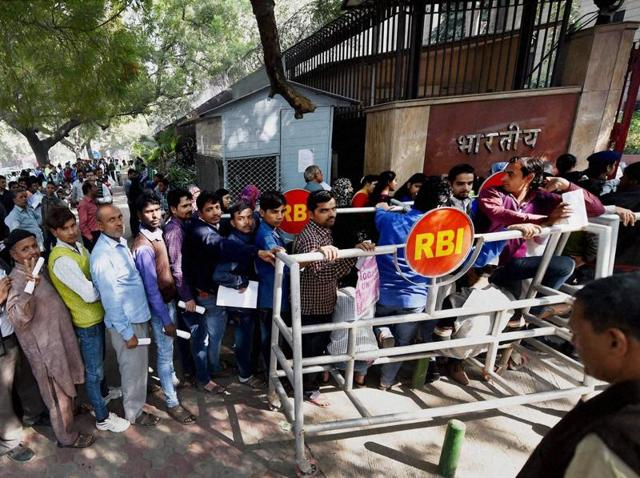 People standing in long queue to withdraw cash from ATMS  on Sunday.