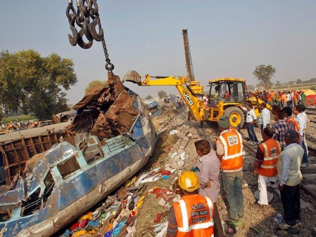 Rescue workers move a carriage at the site of Indore-Patna Express derailment in Pukhrayan, Kanpur.
