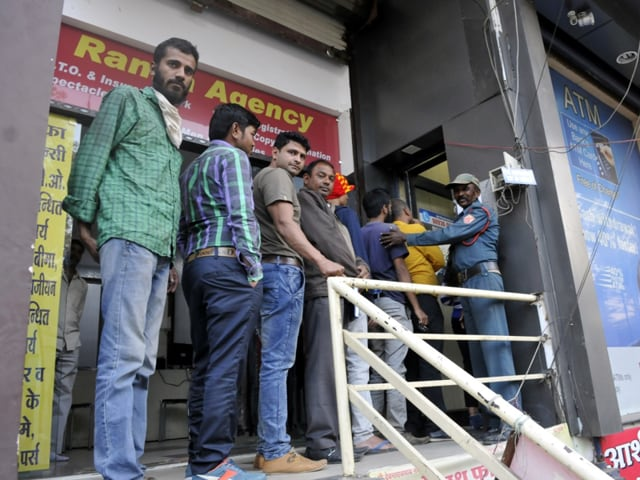 People make purchases by using debit cards at a shop in Indore. Plastic money has helped people tide over the currency crisis.(Arun Mondhe / HT photo)