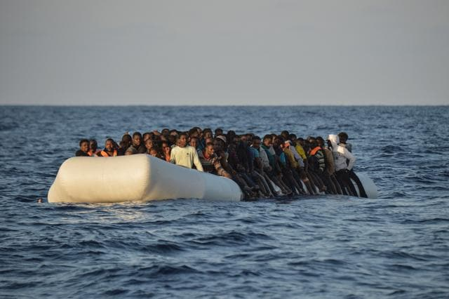 File photo taken on November 03, 2016 shows migrants and refugees on a rubber boat before they were rescued by the ship Topaz Responder run by Maltese NGO Moas and Italian Red Cross off the Libyan coast in the Mediterranean Sea, on November 3, 2016.
