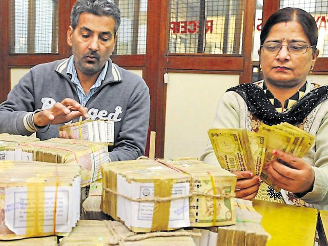 Bank officials counting the old currency notes of Rs 500 in Jalandhar on Monday