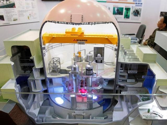 A man sits behind a model of a Japanese Mitsubishi nuclear reactor at the World Nuclear Power 2012 exhibition in Hanoi. Vietnam  formally scrapped plans to build two nuclear power plants on Tuesday, Nov. 22, 2016.