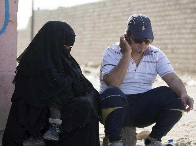 In this photo, a man who identified himself as Omar Danoun talks on the phone during an interview with The Associated press in Gogjali, Iraq. Danoun was taken into custody later in the interview by Iraqi soldiers who overheard and said he seemed to have a Syrian Accent, and who believed he was an Islamic Stage group member.