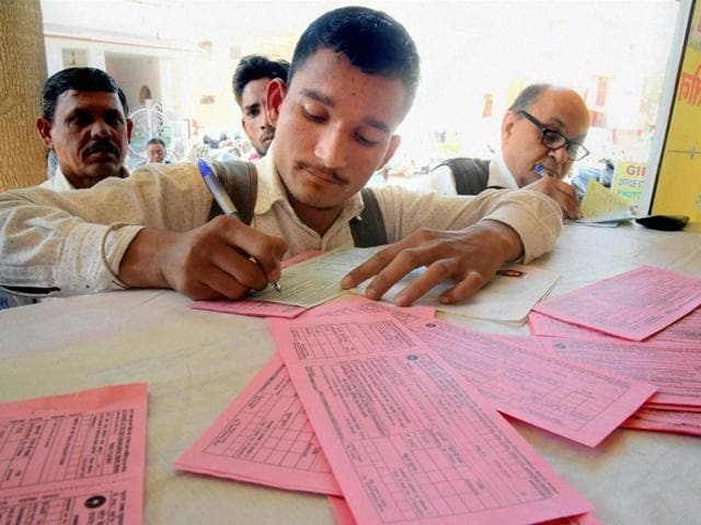 A man fills forms at a bank to exchange old Rs 500 and Rs 1000 notes in Bikaner.