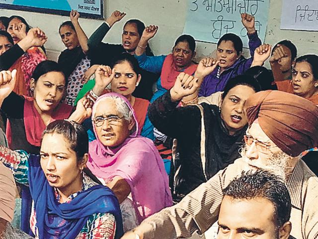 Nurses and their family members holding a protest at Rajindra Hospital in Patiala on Monday.