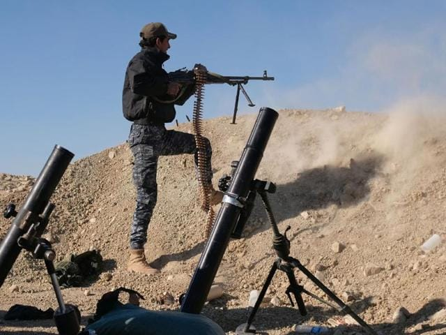 A member of the Iraqi Federal Police fires his weapon at an Islamic State group target on the front line near the village of Tall Adh-Dhahab, some 10 km south of Mosul.