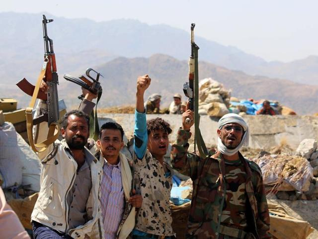 Yemeni tribesmen from the Popular Resistance Committee, supporting forces loyal to Yemen's Saudi-backed President Abedrabbo Mansour Hadi, flash their arms in the country's third-city Taez during clashes with Shiite Houthi rebels, on November 21, 2016.