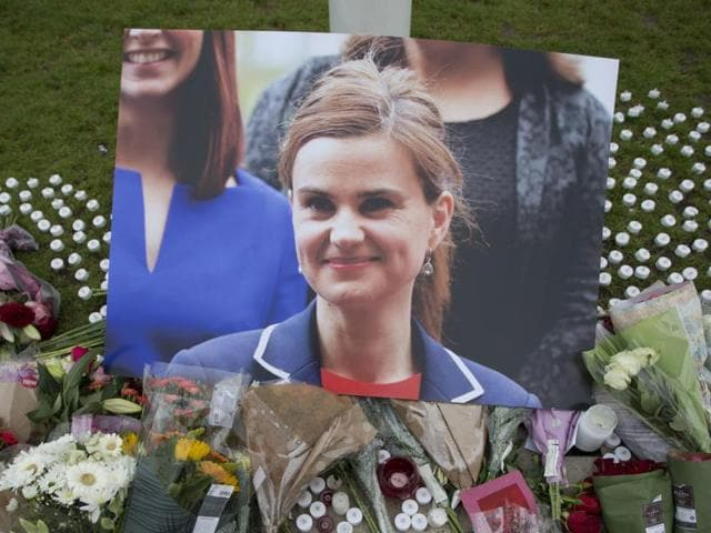 FILE - This is a Friday, June 17, 2016, file photo of an image and floral tributes for Jo Cox, in Parliament Square, outside the House of Parliament in London, after the 41-year-old British Member of Parliament was fatally injured in northern England. A jury Wednesday Nov. 23, 2016 found Thomas Mair with white supremacist views guilty of murdering Labour lawmaker Jo Cox a week before Britain's EU membership referendum. (AP Photo/Matt Dunham, File)