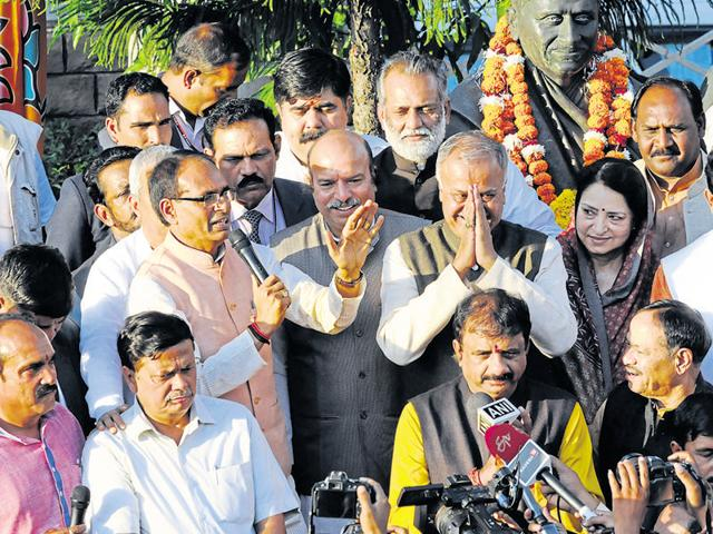 CM Shivraj Singh Chouhan and state BJP president Nand Kumar Singh Chauhan offering sweets to each other at the party head office in Bhopal on Tuesday.