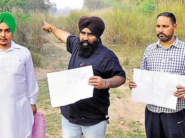 Farmers showing the revenue record with ownership rights of the SYL canal land returned to them by the Punjab government at Bibipur village in Patiala district on Tuesday.