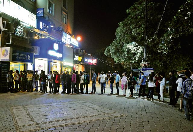 People queue up outside the Standard Chartered bank ATM at DLF phase 4, Galleria Market, on Wednesday.
