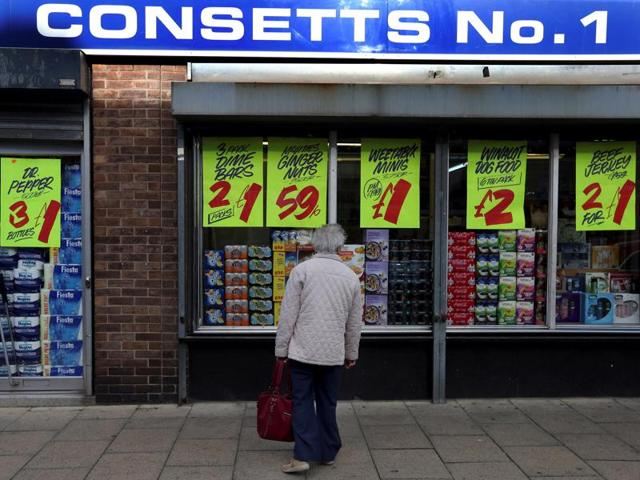 A person looks in a shop window in Consett, Britain.