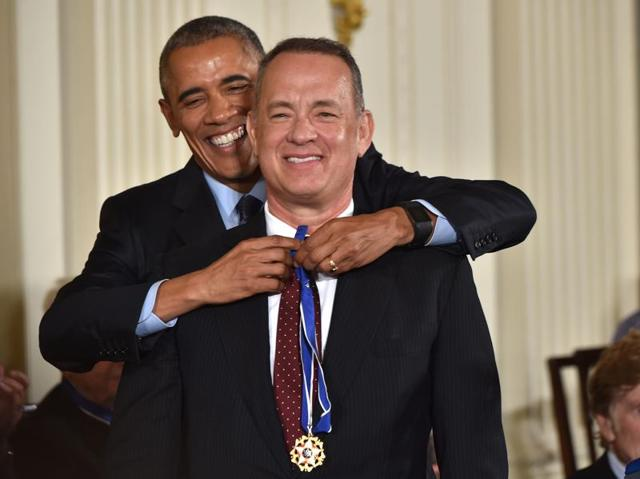 US President Barack Obama presents actor Tom Hanks with the Presidential Medal of Freedom during a ceremony honouring 21 recipients, in the East Room of the White House in Washington, DC.