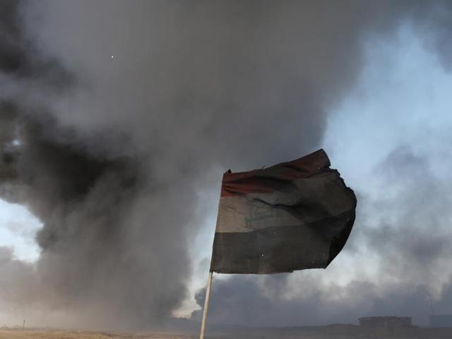 An Iraqi flag is seen in front of oilfields burned by Islamic State fighters in Qayyara, south of Mosul, Iraq November 23, 2016.
