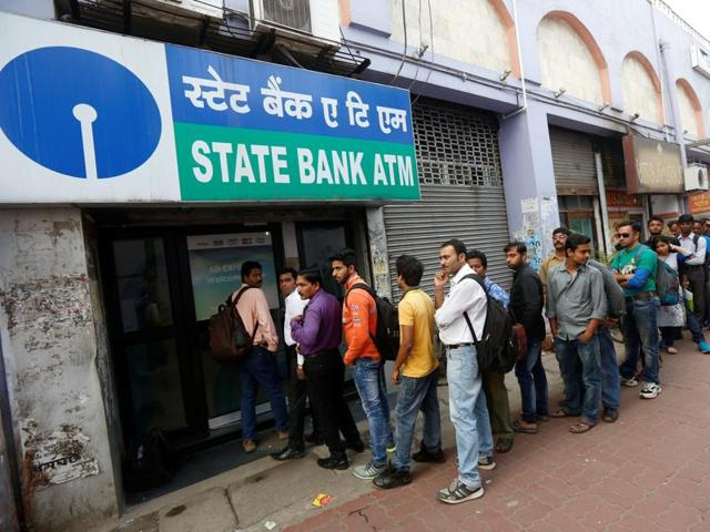 People queue outside an ATM of State Bank of India (SBI) to withdraw money in Kolkata.