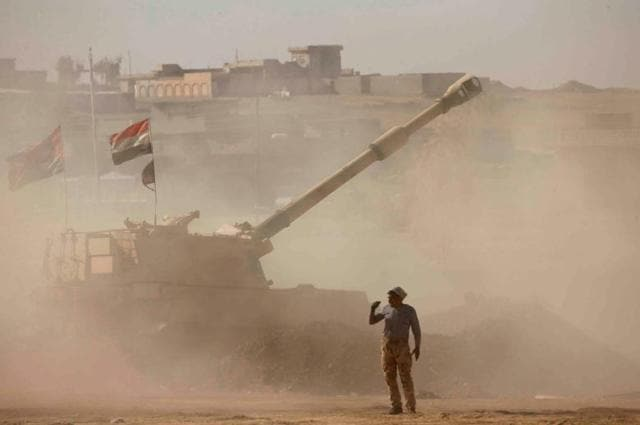 An Iraqi fighter fires artillery towards Islamic State militants, in Ali Rash southeast of Mosul, Iraq.