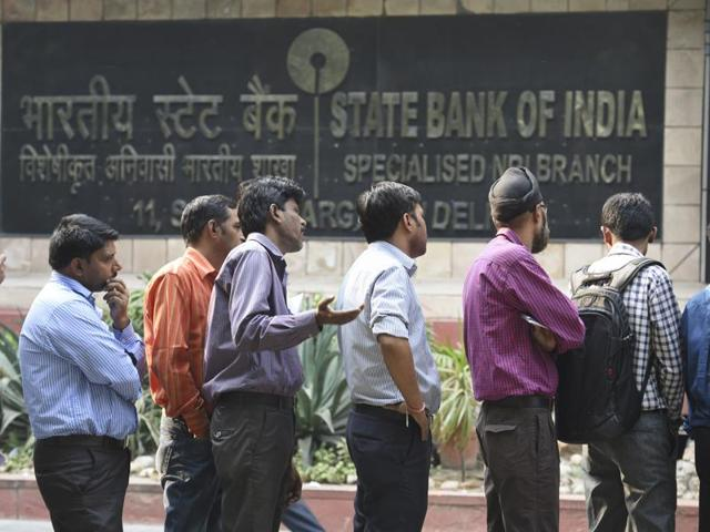 People standing in a queue outside the bank to exchange their old Rs 500 and Rs 1000 notes in New Delhi.