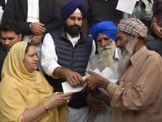 Punjab revenue minister Bikram Singh Majithia handing over the ownership document to a farmer at Kapuri village in Patiala on Wednesday.(Bharat Bhushan/HT Photo)