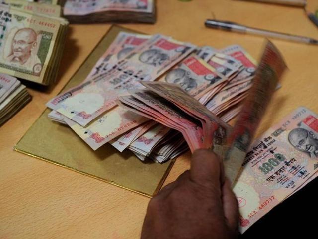 A bank employee counts Indian rupee notes at a bank in Mumbai.