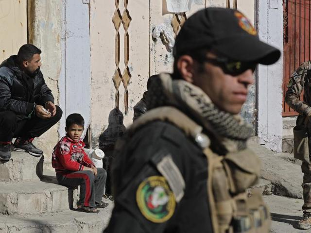 Iraqi Special Forces stand guard in a street, as IS group fighters clash with government forces, in a northeastern district of the city of Mosul on Thursday.