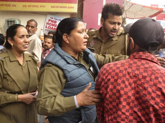 Police officials trying to control the public standing in a queue at a bank in Basti Danishmanda in Jalandhar on Wednesday.