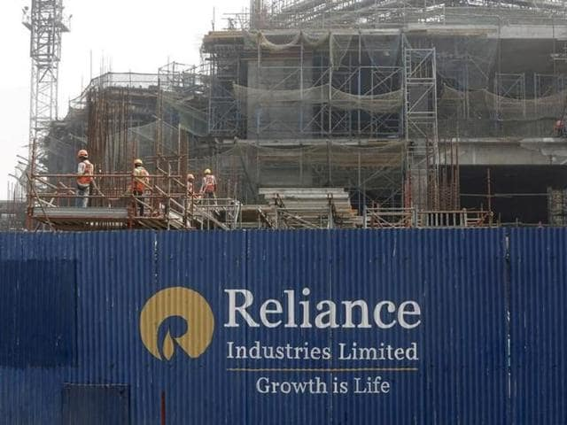 Labourers work behind an advertisement of Reliance Industries Limited at a construction site in Mumbai.