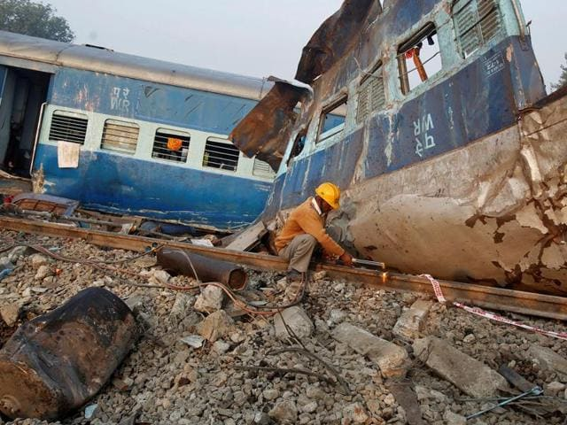 A railway employee cuts a railway track at the site of derailment of  Indore-Patna Express.
