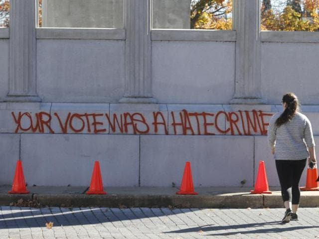 Pedestrians look at graffiti on the statue of Confederate President Jefferson Davis in Richmond, Virginia, on November 10, 2016, two days after Donald Trump was declared the next US president.