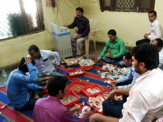 Bank of India employees count donation money at Mahakaleshwar Temple in Ujjain on Thursday.