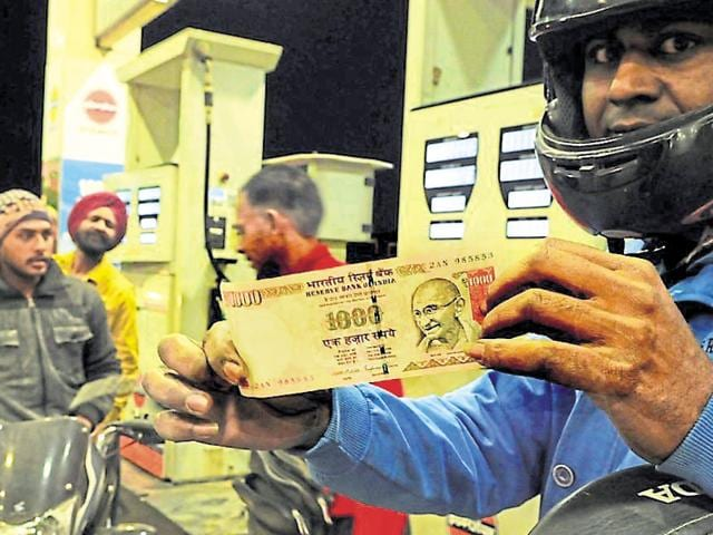 A man shows a scrapped Rs 1,000 banknote at a petrol pump in Sector 38 (West), Chandigarh, on Thursday.